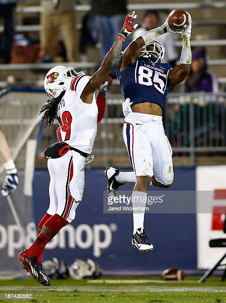 Geremy Davis of the Connecticut Huskies catches a pass in the fourth quarter in front of Terell Floyd of the Louisville Cardinals at Rentschler Field...