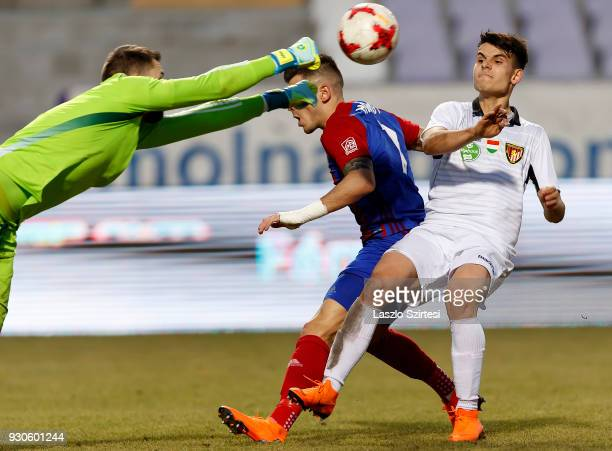 Gergely Nagy of Vasas FC fists the ball before Bence BanoSzabo of Budapest Honved and Szilveszter Hangya of Vasas FC during the Hungarian OTP Bank...