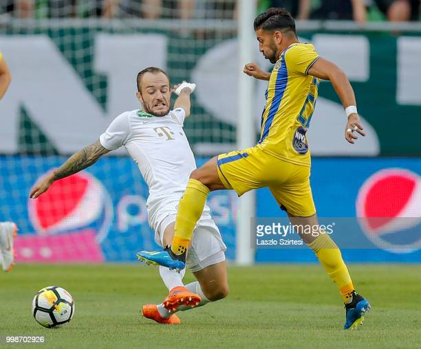 Gergo Lovrencsics of Ferencvarosi TC competes for the ball with Eyal Golasa of Maccabi Tel Aviv FC during the UEFA Europa League First Qualifying...