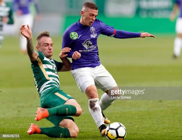 Gergo Lovrencsics of Ferencvarosi TC slide tackles Donat Zsoter of Ujpest FC during the Hungarian OTP Bank Liga match between Ferencvarosi TC and...