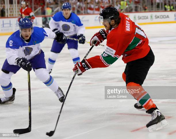 Gergo Nagy of Hungary shoots on goal next to Anton Sagadeyev of Kazakhstan during the 2018 IIHF Ice Hockey World Championship Division I Group A...