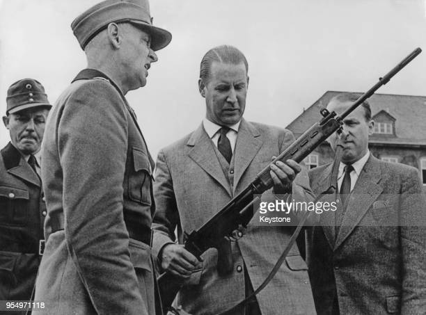 Gerhard Schröder the German Minister of the Interior inspects the new Belgian rifle issued to the newlyformed German Frontier Units 30th July 1956