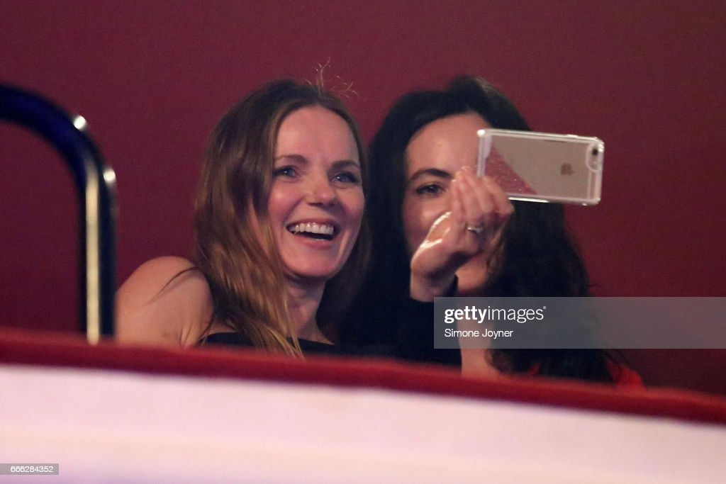 Geri Horner (L) takes a photo on her smartphone as she watches Melanie C with Sally Wood (R) at O2 Shepherd's Bush Empire on April 8, 2017 in London, England.
