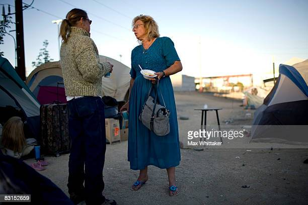 Geri Radway center chats with a friend as she returns to a tent city for the homeless after working two jobs on October 6 2008 in downtown Reno...
