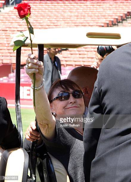 Geri Walsh wife of former 49ers coach Bill Walsh waves a single rose to fans as she leaves the stadium during a public memorial service for Walsh...