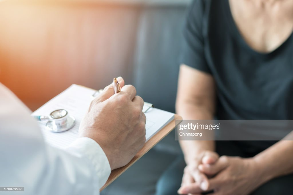 Geriatric doctor (geriatrician) consulting and diagnostic examining elderly senior adult patient (older person) on aging and mental health care in medical clinic office or hospital examination room : Stock Photo