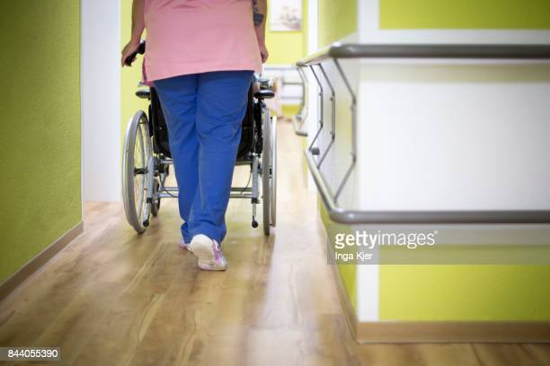 A geriatric pushes a resident in a wheel chair down the hall way on August 08 2017 in EberswaldeFinow Germany