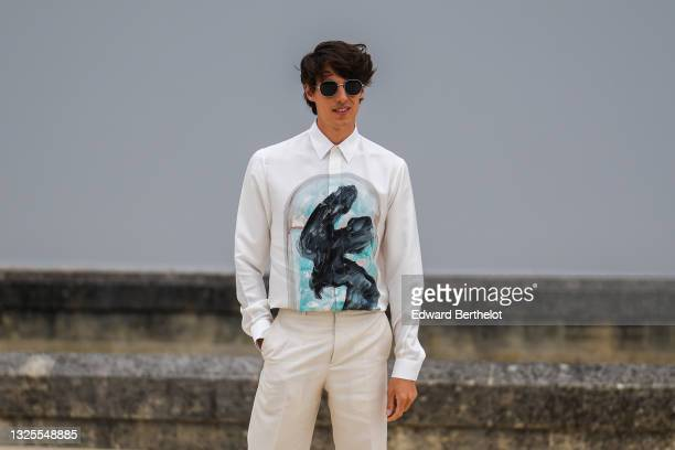 Germain Louvet wears black sunglasses, a white shirt with a black and blue painted window, beige suit pants, a silver ring, outside Dior, during...