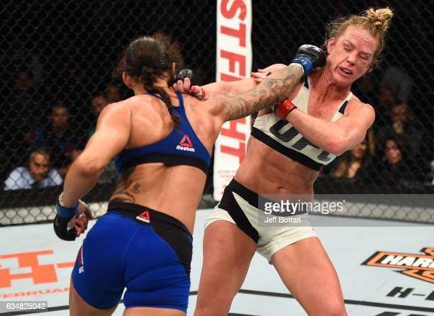 Germaine de Randamie of The Netherlands punches Holly Holm in their women's featherweight championship bout during the UFC 208 event inside Barclays...