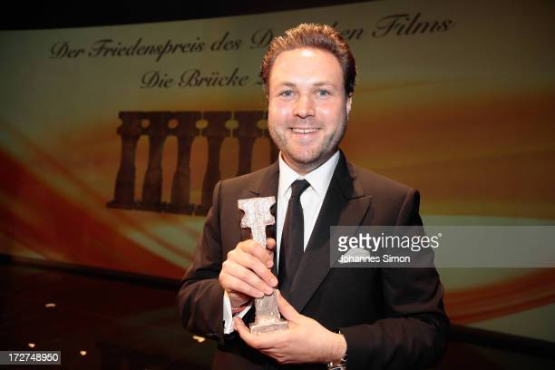German actor and award winner Daniel Harrich poses with the award trophy after the Bernhard Wicki Award ceremony at Munich film festival on July 4...