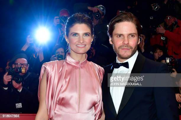 German actor Daniel Bruehl and his partner Felicitas Rombold pose on the red carpet for the opening ceremony of the 68th Berlinale film festival with...