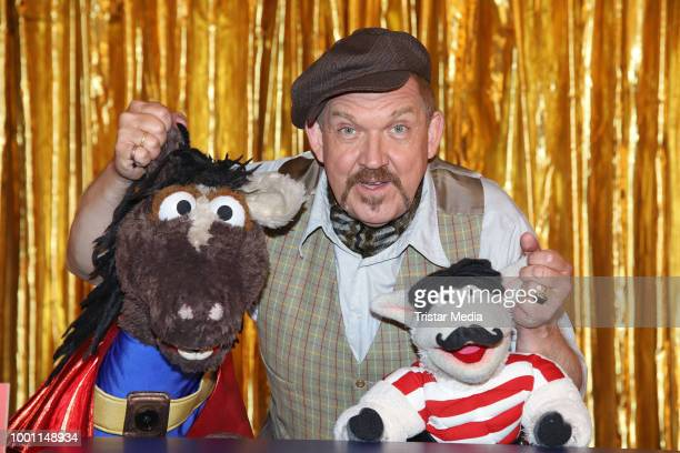 German actor Dietmar Baer with the figures 'Wolle' and 'Pferd' during the 'Alarm im Zirkus' photo call presented by Sesamstrasse on July 18 2018 in...