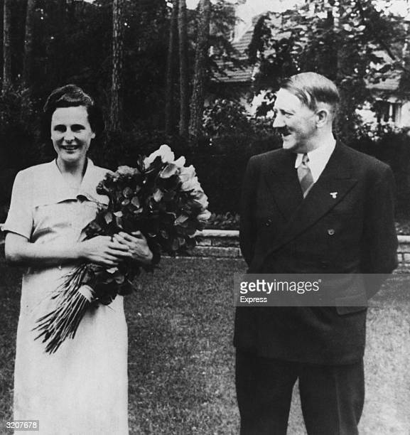 German actor director and photographer Leni Riefenstahl holds a bouquet of roses while Nazi leader Adolf Hitler looks at her and smiles outdoors on a...