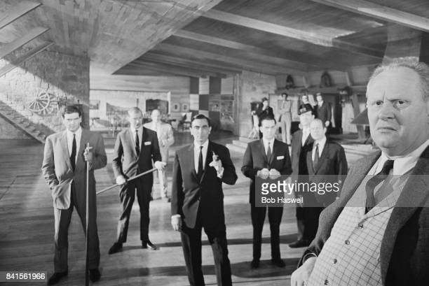 German actor Gert Fröbe as Auric Goldfinger stands with a group of actors as members of the Mafia including actors Martin Benson and Bill Nagy on the...