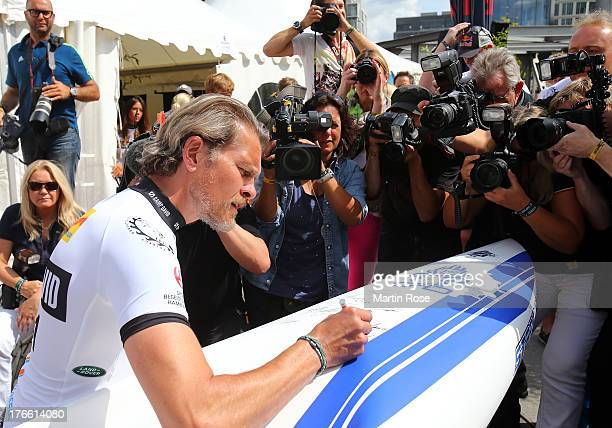 German actor Goetz Otto sings autographs before the Stand Up Paddling celebrity race at Magellan Terassen on August 16 2013 in Hamburg Germany