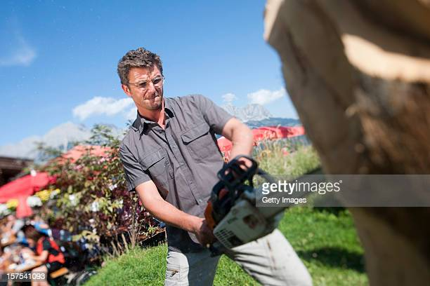 German actor Hans Sigl carves wood with a chainsaw as he visits the filming location of GermanAustrian tv serie 'Der Bergdoktor' on September 17 2011...