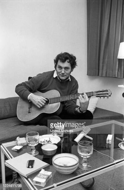 German actor Harald Leipnitz playing guitar, Germany, 1960s.