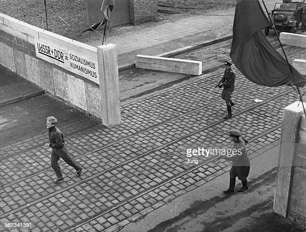 German actor Helmut Griem , as Hans, breaks into a run towards the border of the eastern and western sectors of Berlin as he is pursued by armed East...