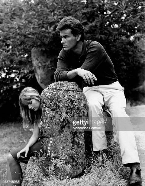 German actor Horst Buchholz sitting in a garden beside Frenchborn Italian actress and singer Catherine Spaak 1963