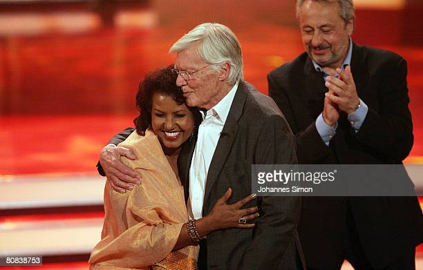 German actor Karlheinz Boehm is hugged by his wife Almaz as actor Wolfgang Stumph looks on during the TVshow Congratulations Karlheinz Boehm A Life...