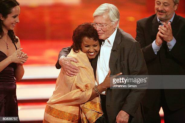 German actor Karlheinz Boehm is hugged by his wife Almaz as actor Wolfgang Stumph and Stephanie Stumph look on during the TVshow Congratulations...