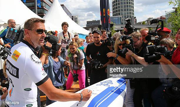 German actor Mark Keller sings autographs before the Stand Up Paddling celebrity race at Magellan Terassen on August 16 2013 in Hamburg Germany