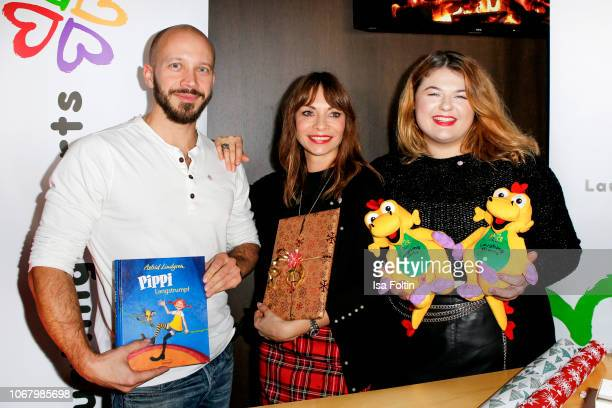 German actor Max Florian Hoppe German presenter Jean Bork and German singer Alina Wichmann alias Alina wrap a present for children in need during the...