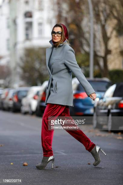 German actress Alexandra Kamp wearing a wine red colored velvet jumpsuit by onepiece, dark grey ankle boots with glitter heels by Miu Miu, a light...