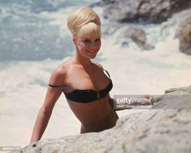 German actress and model Elke Sommer in a black bikini top on a rocky beach in a scene from 'Deadlier Than the Male' 1967