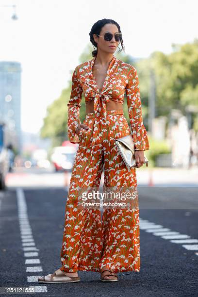 German actress and presenter Annabelle Mandeng wearing an orange crop top with floral print and long sleeves and matching pants by Horrockses, gold...