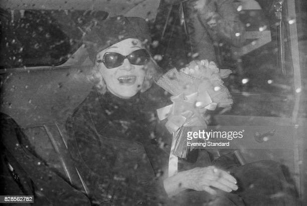 German actress and singer Marlene Dietrich smiles cheerfully from inside a car while holding a bouquet upon her arrival at Heathrow Airport London...