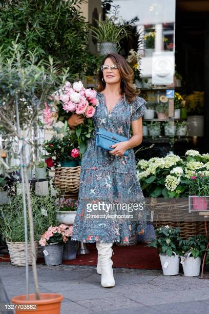 German actress Christine Neubauer wearing a multicolored floral print midi length dress with short ruffle sleeves, v-neck and gathered details by...
