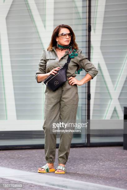 German actress Christine Neubauer wearing a vintage olive green jumpsuit, a multicolored scarf by Gucci, sunglasses by Gucci, a black crossbody bag...