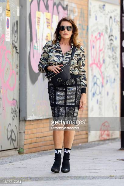 German actress Christine Neubauer wearing a vintage olive green bomber jacket with camouflage pattern, a black midi length pencil skirt with silver...