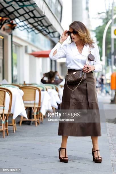 German actress Christine Neubauer wearing a white blouse by Riani, a brown leather maxi skirt by Riani, a gold bracelet by Chloe, brown sandals by...