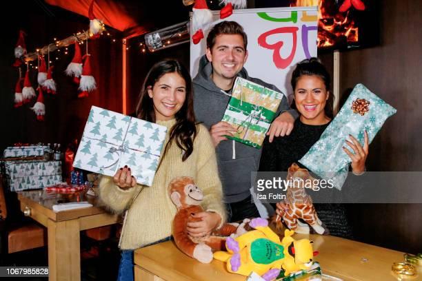German actress Chryssanthi Kavazi German presenter Christian Wackert and German presenter Steffi Brungs wrap a present for children in need during...