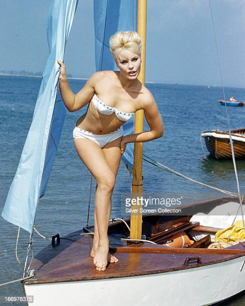 German actress Elke Sommer wearing a bikini and standing on the deck of a sailing dinghy circa 1963