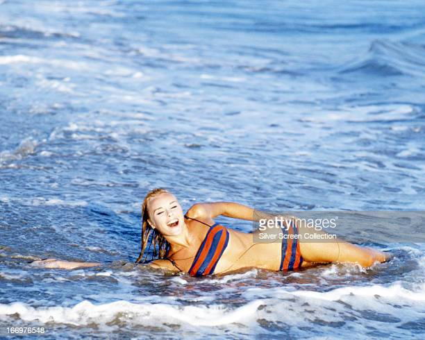 German actress Elke Sommer wearing a bikini as she lies in the surf at a beach, circa 1965.
