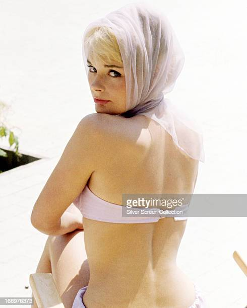German actress Elke Sommer wearing a headscarf and bikini and looking over her shoulder circa 1963