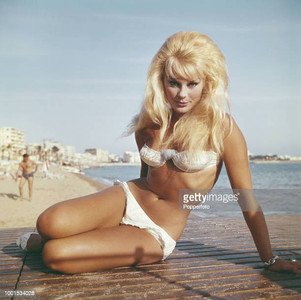 German actress Elke Sommer wears a white bikini as she poses on a beach near the Croisette during the 1961 Cannes Film Festival at Cannes in France...
