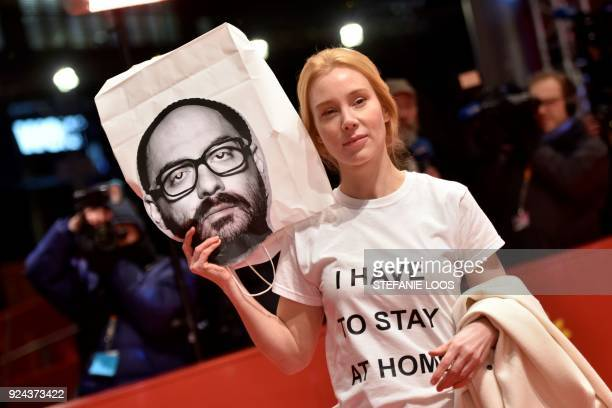 German actress Franziska Petri holds a bag with the portrait of detained Russian director Kirill Serebrennikov as she arrives on the red carpet...