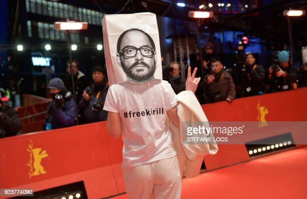 TOPSHOT German actress Franziska Petri shows a victory sign and wears on her head a bag with the portrait of detained Russian director Kirill...