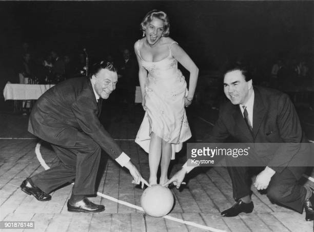 German actress Hannelore Bollmann prepares to kick a ball into an empty barrel assisted by actor Willy Fritsch and former heavyweight boxing champion...