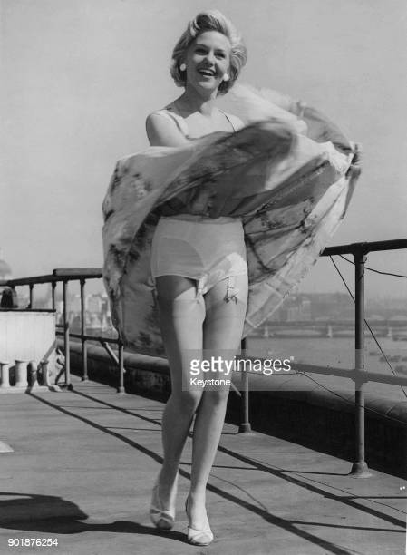 German actress Hannelore Bollmann reveals her underwear when surprised by a gust of wind on the roof of her London hotel 10th April 1956