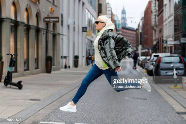 German actress Lara-Isabelle Rentinck wearing a cream colored hoodie with neon green details by Cecile, a black jacket by Replay, dark blue denim...