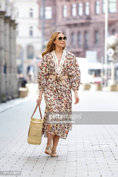 German actress Lara-Isabelle Rentinck wearing sunglasses by Chloe, a long multicolored maxi dress with floral print by Tory Burch, a dark brown and...