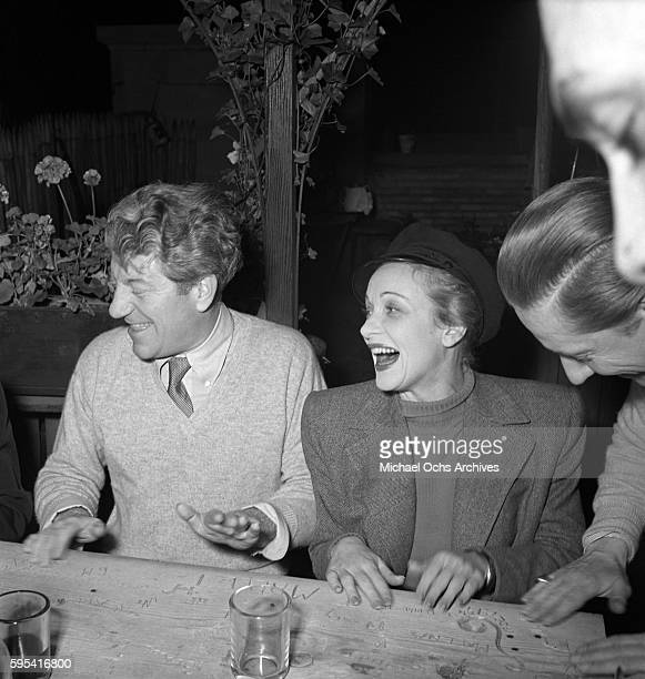 German actress Marlene Dietrich with French actor Jean Gabin share a joke at La Vie Parisienne restaurant located at 3 East 52nd Street circa 1942 in...