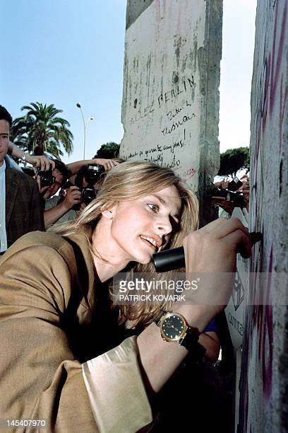 German actress Nastassja Kinski signs one of the two pieces of the Berlin Wall put in the garden of Hotel Martinez in Cannes during the 43th...