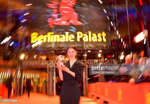 German actress Paula Beer poses with her trophy Silver Bear for Best Actress on the red carpet after the awarding ceremony of the 70th Berlinale film...