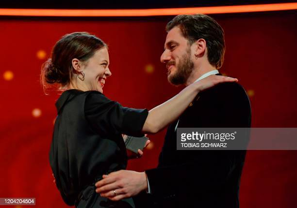 German actress Paula Beer reacts as she receives with the trophy Silver Bear for Best Actress by Italian actor and jury member Luca Marinelli during...